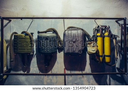 Old vintage backpacks oxygen gas cylinders for gas masks for radioactive contamination in bomb shelter, close up