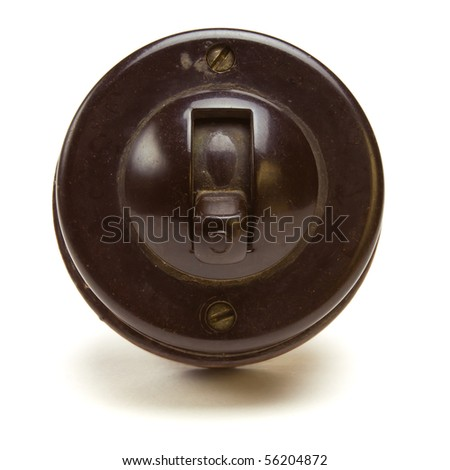 Old Vintage bakelite light switch isolated against white background from low perspective.