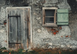 Old vintage barn wall with wooden window and worn wooden door.