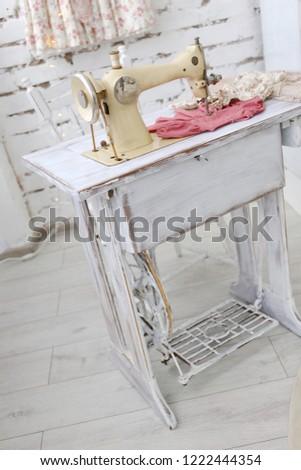 old vintage beige sewing machine in atelier with white brick walls #1222444354