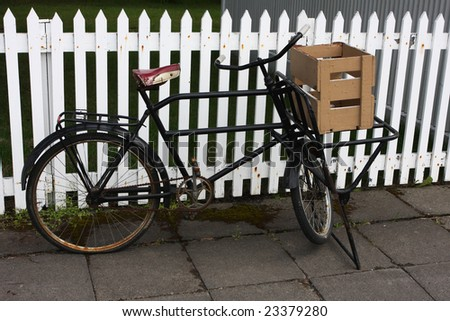 Old vintage bicycle standing by a white picket fence