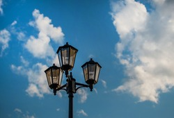 Old vintage black decorative lantern with clear glass on pillar. Three street lamps on one pole. Sunny blue sky with white clouds