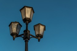 Old vintage black decorative lantern with clear glass on pillar. Three street lamps on one pole in sunset light. Blue sky