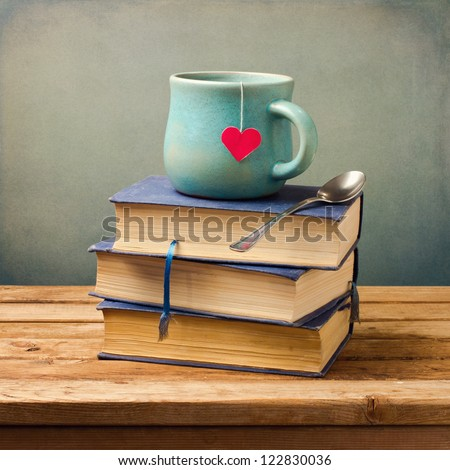 Old vintage books and cup with heart shape on wooden table - stock photo