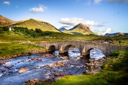 Old vintage brick bridge crossing river in Sligachan, Isle of Skye, Scotland with scottish landscape, vegetation, hills and mountains with fresh, blue water and sunny sky