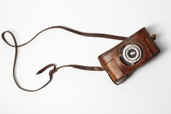 Old vintage camera with 35mm lens in brown leather case isolated on white background