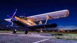 Old vintage classic airplane on small airfield in night time with clear sky. Abandoned biplane in long exposure under the stars