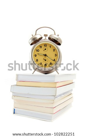 Old, vintage clock on the top of the books, image is taken over a white background