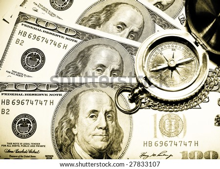 old vintage compass on a hundred usa dollar bill. focus on the eyes of prezident