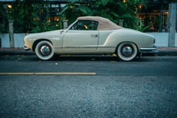 Old vintage convertible roadster car parked on the street. Side view. Vintage effect. Sunset.