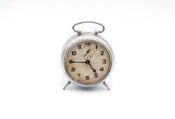 Old vintage cracked broken alarm clock on white background. Old damaged clock. Antique piece of watch history. Historic clock with a broken glass. Mechanical clock still working. High resolution image