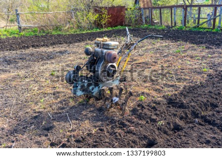 Old vintage dirty motor cultivator on suburban plot. Ploughing ground, land cultivation, soil tillage. Spring work in the garden. Gardening concept #1337199803