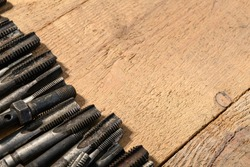 Old vintage hand tools - drills and threading die on a wooden background