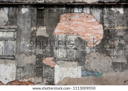 Old vintage house, background texture of a cracked and eroded wall, old bricks in the ancient cement with cracks, old wooden window. Thai Traditional local house at Songkhla. Texture. Copy space.