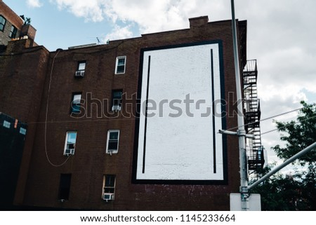 Old vintage house facade from brownstone and with commercial blank billboard for advertising information in city, building with apartments and mock up publicity area