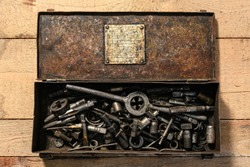 Old vintage iron toolbox full of drills and threading die tools on a wooden background