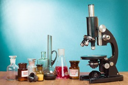 Old vintage microscope and laboratory glass bottles on table for science background