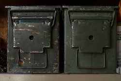 old vintage military ammo cans metal storage containers sitting on the shelf collecting dust olive dab green