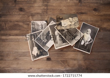 old vintage monochrome photographs are scattered on a wooden table, photographs of his and his sisters, pictures taken in 1964, concept of genealogy, the memory of ancestors, family ties, memories