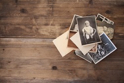 old vintage monochrome photographs, pictures taken in 1968, in sepia color are scattered on a wooden table, concept of genealogy, the memory of ancestors, family ties, memories of childhood