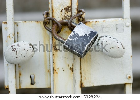 Old vintage padlock fixed on grungy metal fence - stock photo