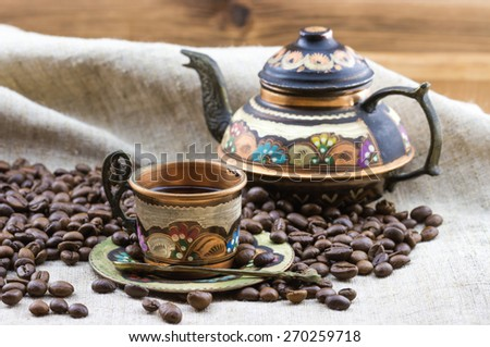 Old vintage painted coffee set copper cup and teapot with heap of roasted coffee beans on sackcloth