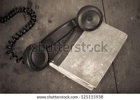Old vintage phone handset, book on wooden table grunge background