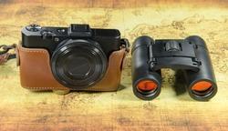 old vintage pocket camera and binocular on a old world map