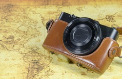 old vintage pocket camera on aold world map