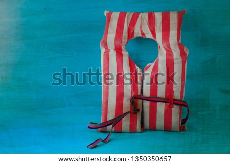 Old vintage red and white striped life vest on a wooden backgrou