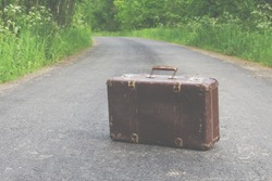 old vintage retro brown suitcase stands on an asphalt road forgotten or abandoned as unnecessary