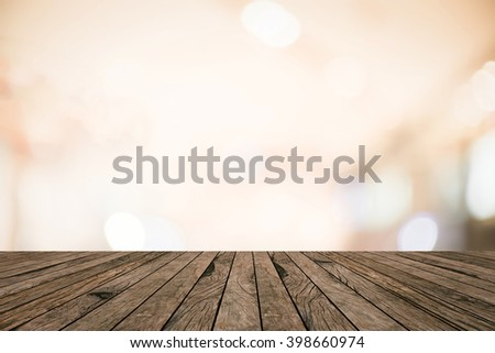 old vintage retro brown wood tabletop with blurred abstract store mall bokeh light warm tone background boarder:grunge aged wooden with blurry orange color backdrop.show advertise product on display