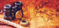 Old vintage retro compass and binoculars on ancient world map. Travel geography navigation concept background. Vintage still life