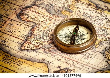Old vintage retro compass on ancient map.