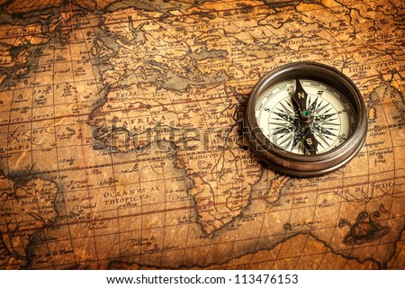 Old vintage retro compass on ancient map.The map used for background is in Public domain. Map source: Library of Congress. Country: Belgium Year: 1570. Author: Abraham Ortelius (1527-1598)