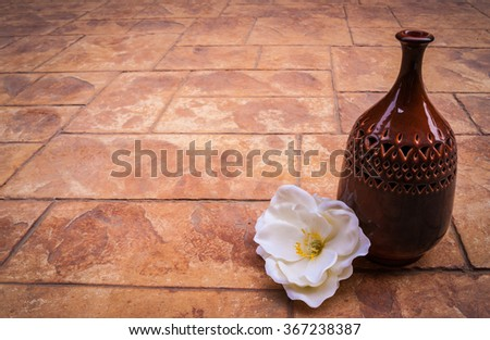 Old vintage retro hand made Islamic style vase with muslim ornaments on a brick background with white rose flower, beautiful arabian jar photo, ramadan kareem