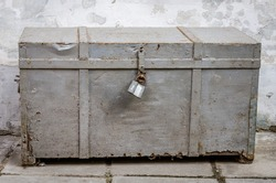 Old vintage retro metal box drawer, closed on the padlock is in the yard near the wall