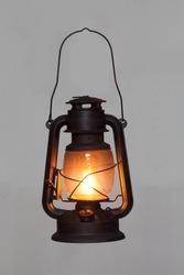 old vintage rusty kerosene black lamp isoleted on gray background. Glass oil lamp. Storm lantern. object vintage concept