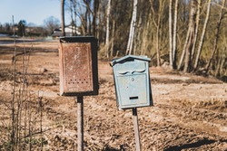 Old vintage rusty memory postbox or mailbox concept. Multicolored old shabby mailboxes. Countryside, outdoor shot.