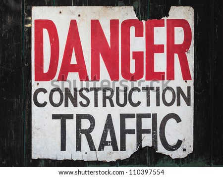 Old vintage sign on wooden wall with the text danger construction traffic
