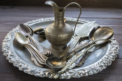 Old vintage silver kitchen equipment utensil tableware silverware with ornament pattern and small eastern jug on a tray on dark table