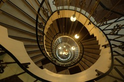 Old vintage Spiral circle Staircase decoration interior, high lighthouse stairs. A spiral staircase spiraling down about five floors. The winding concrete stairs are empty. The metal hand rail is nice