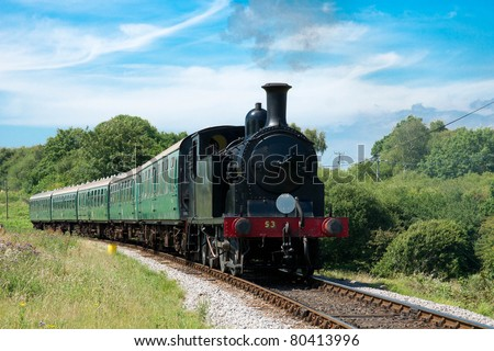 old vintage steam train with green wagons