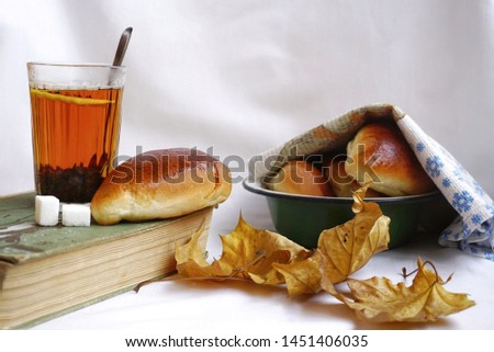 Old (vintage) still life with untitled book, cup of tea, sugar, pastries and autumn leaves on white background. Home comfort. Memories of the past. #1451406035