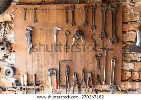 Old vintage tools hanging on a wooden clipboard, hobby time in garage.
