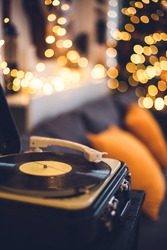 Old vintage vinyl record player in a cozy home, livingroom with lots of warm fairy lights and orange pillows, couch, family time concept, music, christmas and new year songs, music listening