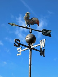 old vintage weathercock in iron on blue sky background