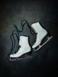 Old vintage white ice skates with black laces on dark rustic background