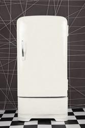 old vintage white refrigerator on a deep background. Vertical frame