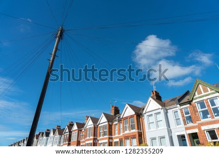 Old vintage wood electric poles cable construction style in townhouse area in UK. Pylon, power cables, power pole and messy cable with townhouse in background.